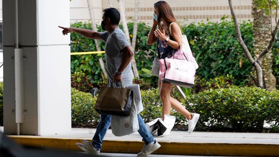 Shoppers walk towards a garage after leaving the Aventura Mall where a shooting left three people injured and several suspects in custody, Saturday, May 8, 2021, in Aventura, Fla. Aventura Police said two groups of people had begun fighting in the mall when shots rang out.