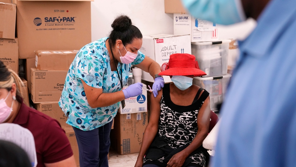 In this April 10, 2021, file photo, registered nurse Ashleigh Velasco, left, administers the Johnson & Johnson COVID-19 vaccine to Rosemene Lordeus, right, at a clinic held by Healthcare Network in Immokalee, Fla.