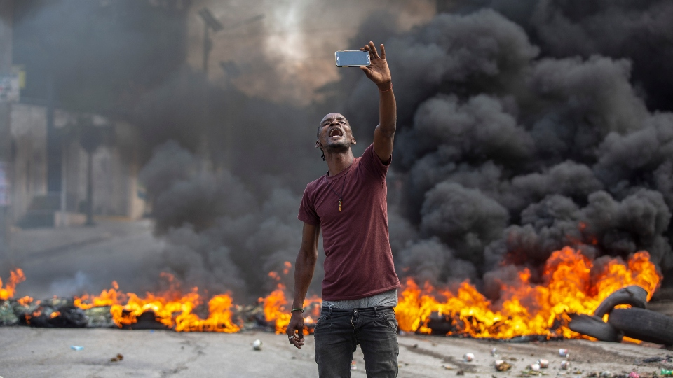 A protester takes a selfie at a burning barricade set by protesters in Port-au-Prince, Haiti, Monday, Oct. 18, 2021. Workers angry about the nation's lack of security went on strike in protest two days after 17 members of a U.S.-based missionary group were abducted by a violent gang. (AP Photo/Joseph Odelyn)