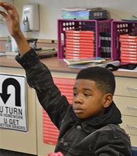 Fifth-grader Eric Gordon raises his hand to discuss a book about baseball player Satchel Paige with mentor Gary Harmon, Pinewood Middle School principal