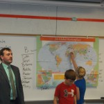Nathan Origer with students recognizing how trade with other countries affects their daily lives.