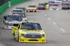 Kyle Busch, driver of the #51 Dollar General Toyota, leads a pack of trucks during the NASCAR Camping World Series UNOH 225 at Kentucky Speedway on June 26, 2014 in Sparta, Kentucky. Photo by Christian Petersen/Getty Images