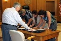 Starke County CASA volunteers Eddie Fields, Patti Scaggs and Lori Reading sign their oaths of office.