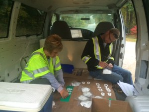 KVREMC employees Denise Cultice and Josh Gordon apply the house numbers to the reflective signs before they are installed.