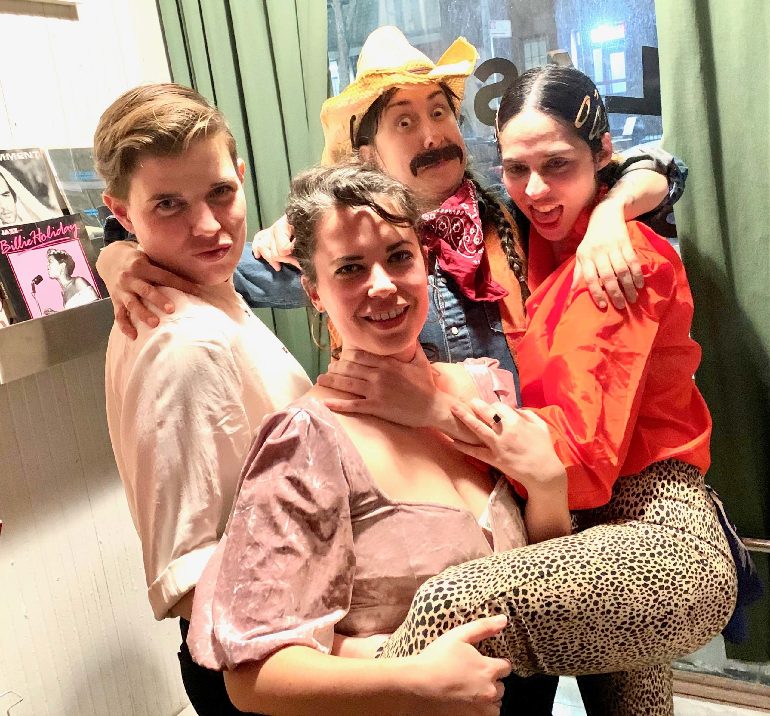 the three wmn founders with drag king performer Nacho posing at a window