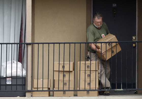 A red Cross representative puts supplies outside quarantined family's apartment