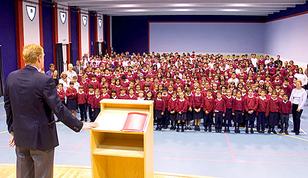 A1ENDA Headmaster takes pupils and staff assembly in modern school hall