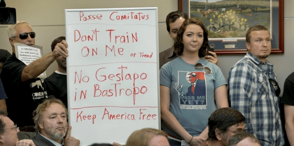 Bob Welch holds a sign at a public hearing about the Jade Helm 15 military training exercise in Bastrop, Tex./Photo: AP