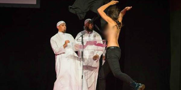 An Islamic conference's debate on wife-beating was delayed when topless women stormed a stage in France on Sept. 13, 2015. (Image: Femen, Twitter)