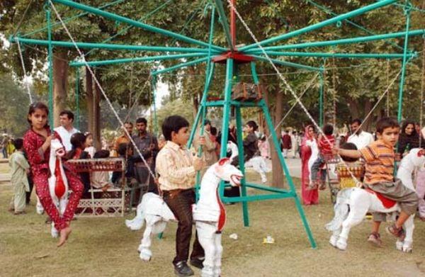 Young children enjoy rides at Gulshan-e-Iqbal Park, Lahore, before bomb blast