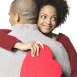 holiday portrait of a young adult woman as she holds a heart shaped box and hugs her boyfriend