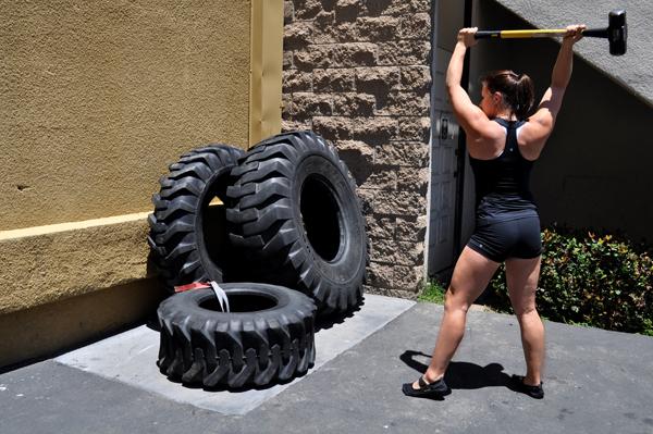 Une crossfitteuse pratique la frappe sur pneu