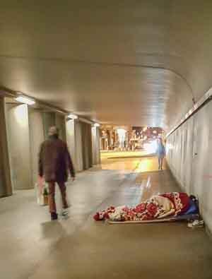 Bettler schläft im Schlafsach in einer Unterführung