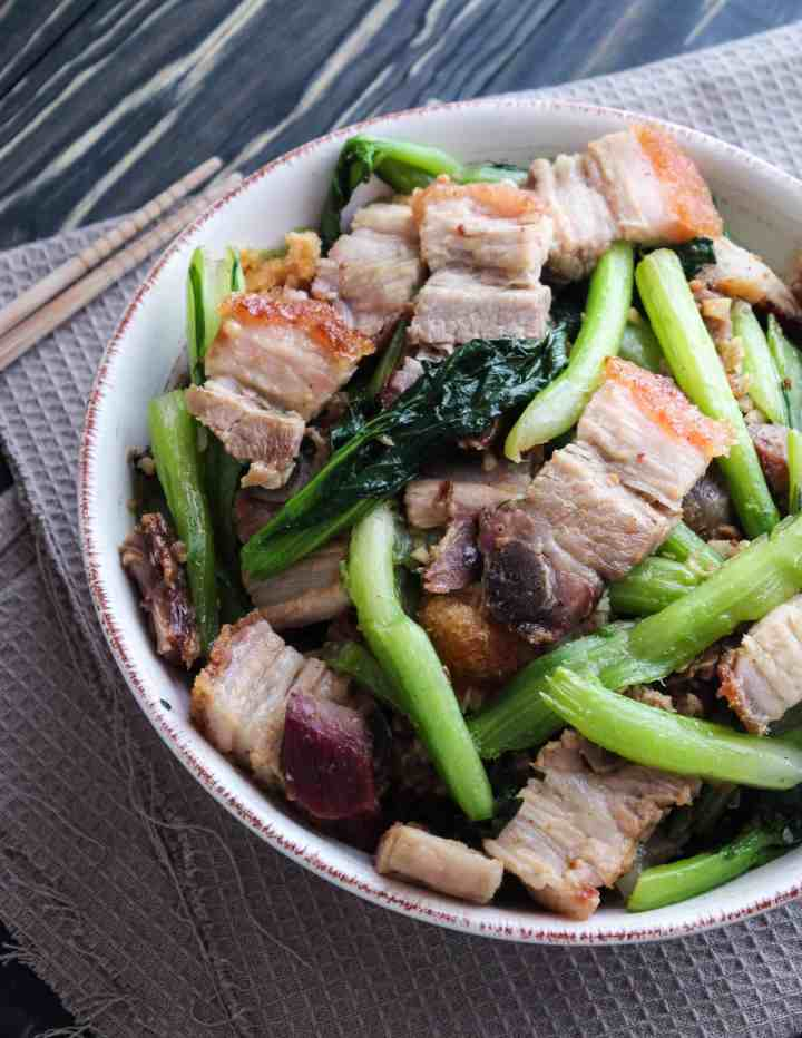 zoomed in crispy pork belly stir fried with Asian greens on a dish