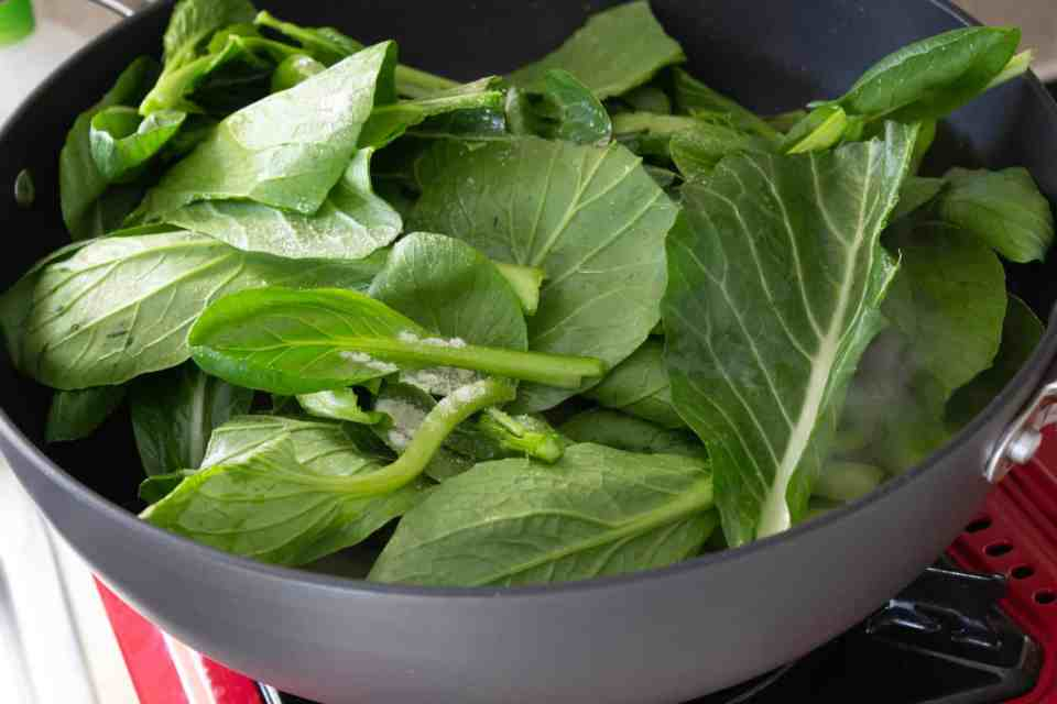 Choy sum leaves in a wok
