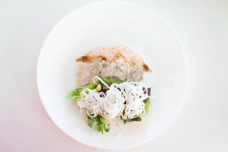 Pork and prawns above greens and rice noodle in a rice paper