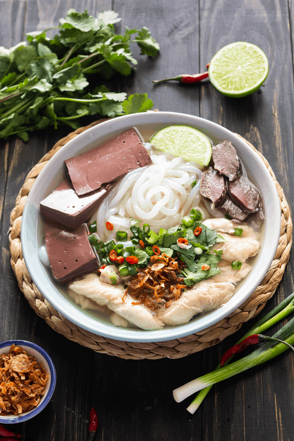 A bowl of Vietnamese tapioca noodle soup (banh canh) on a wooden table with herbs surrounding the bowl
