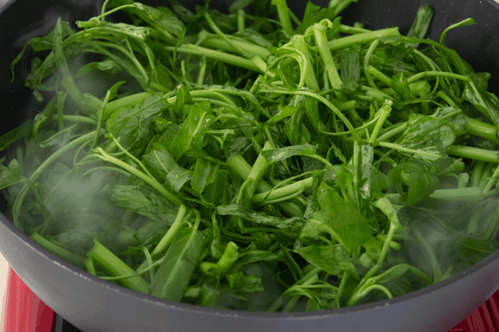 Water spinach in a wok