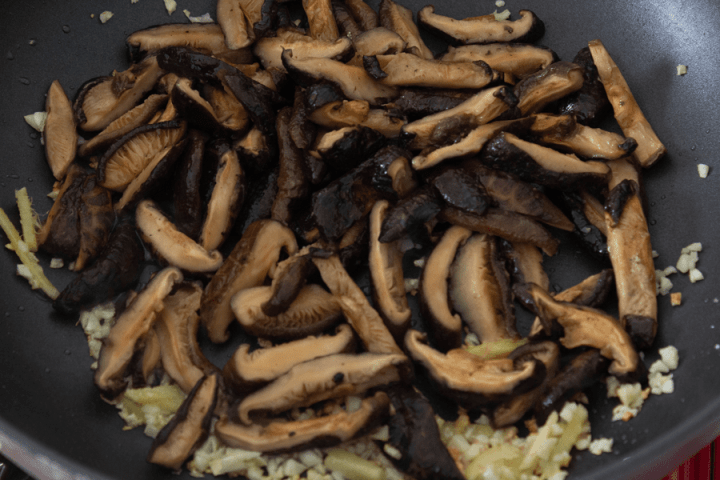 Sliced mushrooms in a wok with mined garlic