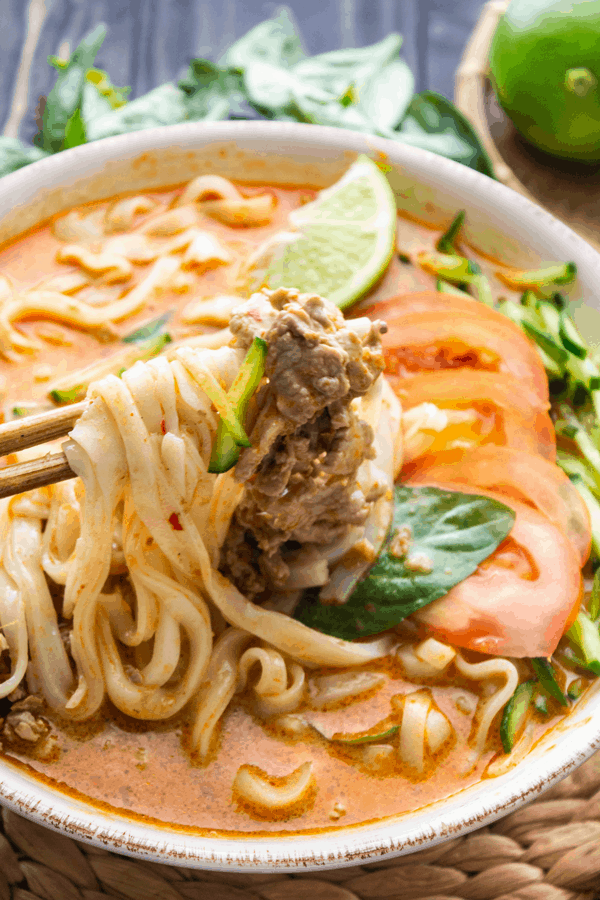 Satay beef noodle soup with chopsticks holding up noodles