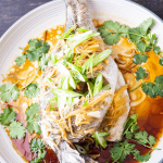 Fish with ginger and shallots on top on a plate of soy