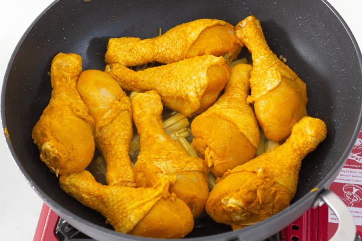 Tumeric chicken drumsticks in a wok