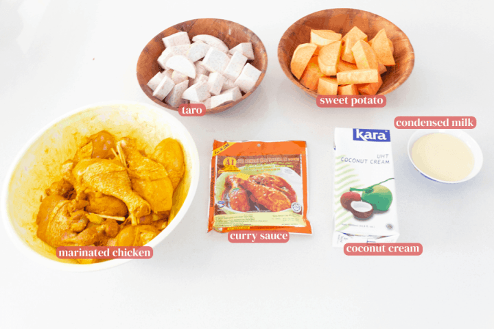 Marinated chicken in a bowl, taro and sweet potato chunks in bowls, curry sauce in a bag, coconut cream in a carton and condensed milk in a bowl