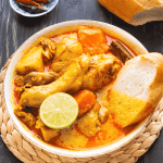 Chicken curry in a bowl with a piece of baguette and half a lime