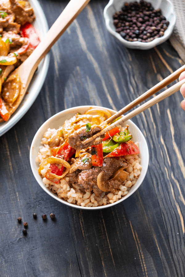 Beef and capsicum in a bowl with chopsticks