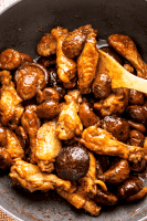 Wings and mushrooms in a wok with a wooden spoon