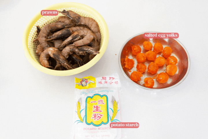 Prawns in a colander, salted eggs in a dish and potato starch in its packet