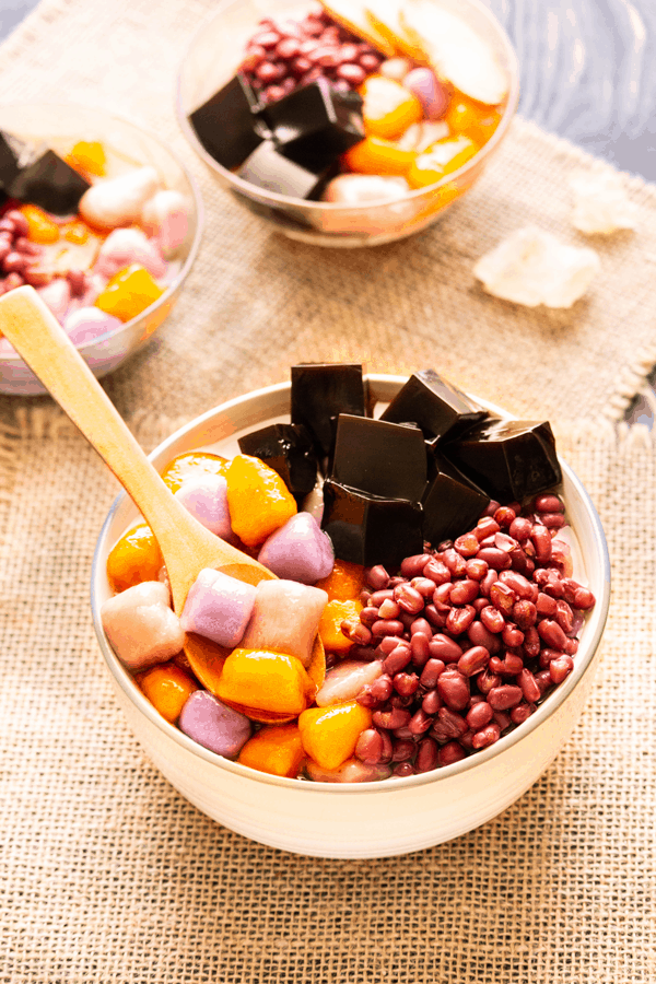 Taro and sweet potato balls in a bowl with grass jelly, red beans and a wooden spoon