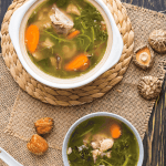 Watercress soup in a bowl and a pot with a spoon on the side, dates and mushrooms