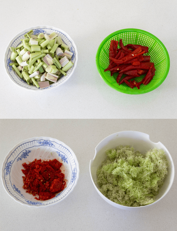 Lemongrass cut into chunks in a bowl along with a bowl of chili where both are then blitzed until fine
