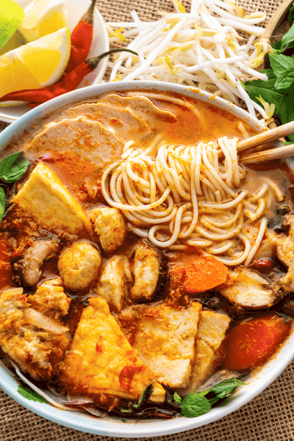 Noodles twirled around chopsticks in a bowl of soup with tofu, mushrooms and carrots