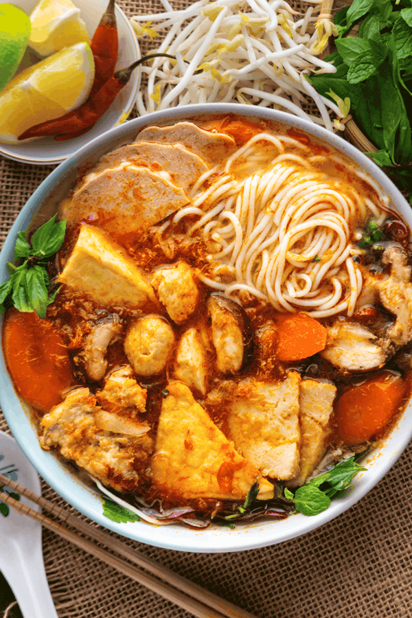 Noodles, mushrooms and tofu in a bowl of soup with carrots and mint