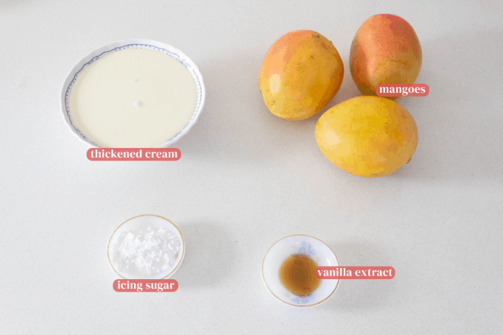 Mangoes, thickened cream in a bowl and icing sugar and vanilla extract in dishes