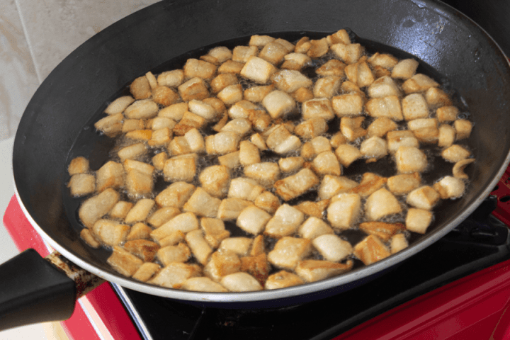Pork fat cubes cooking in oil in a pan