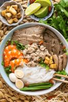 Prawns, pork slices, noodles, quail eggs and garnish in a bowl with chopsticks