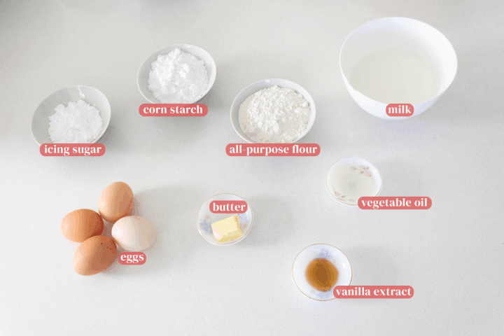 Corn starch, icing sugar, flour, milk, butter, vanilla extract and vegetable oil in dishes with milk in a bowl and eggs on the counter