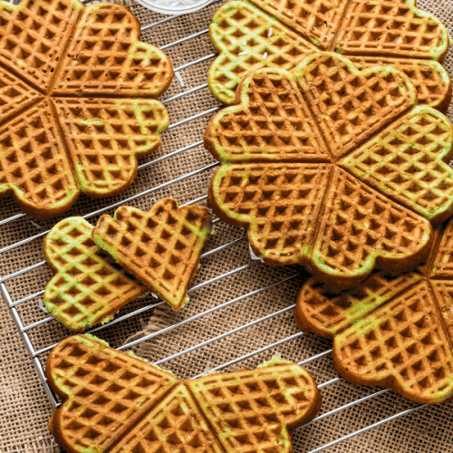 Pandan waffles on a cooling rack with coconut shreds in a dish
