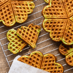 Pandan waffles on a cooling rack with coconut shreds in a dish and a waffle in a paper bag