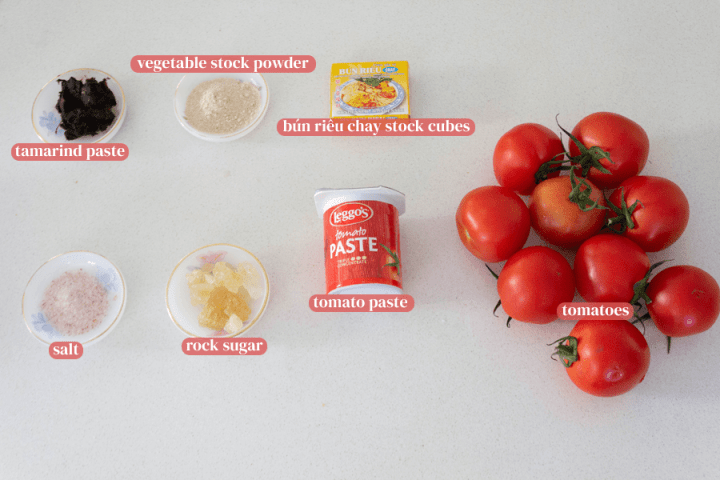 Tomatoes, tomato paste in a container, rock sugar, vegetable stock powder, salt and rock sugar in dishes and bun rieu chay stock cubes in a box