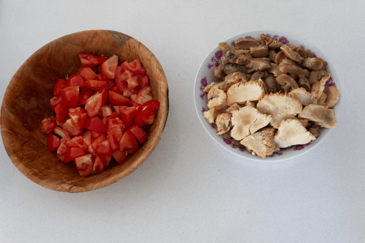 Diced tomatoes in a bowl with slides mushrooms in a bowl