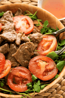 Beef and tomato slices in a bowl with watercress and tongs