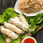 Rice paper rolls on lettuce and herbs with a plate of bi and a bowl of chili sauce