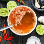 Vietnamese dipping sauce in a bowl with a ladle, used limes, chili and sugar in a dish with a spoon in it