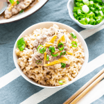 Pork mince, julienned ginger and spring onions in a bowl of rice with a dish of spring onions and chopsticks