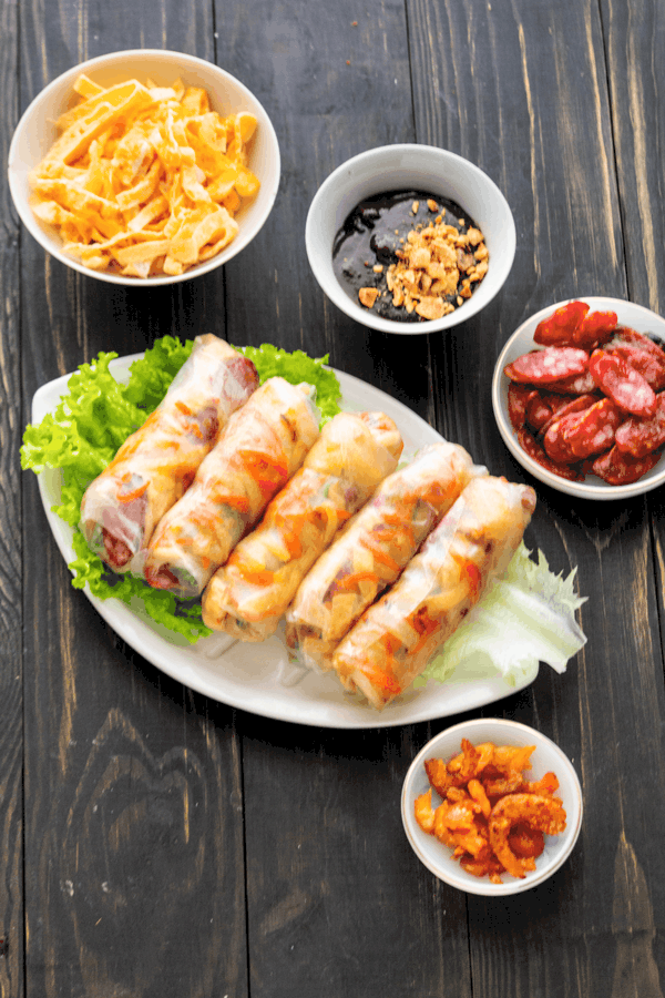 Bo Bia on a plate with lettuce alongside eggs, hoisin sauce, shrimp and sliced Chinese sausage in dishes