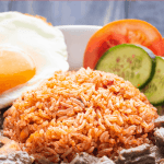 Cơm Đỏ on a plate with Shaking Beef, a fried egg and cucumber and tomato slices